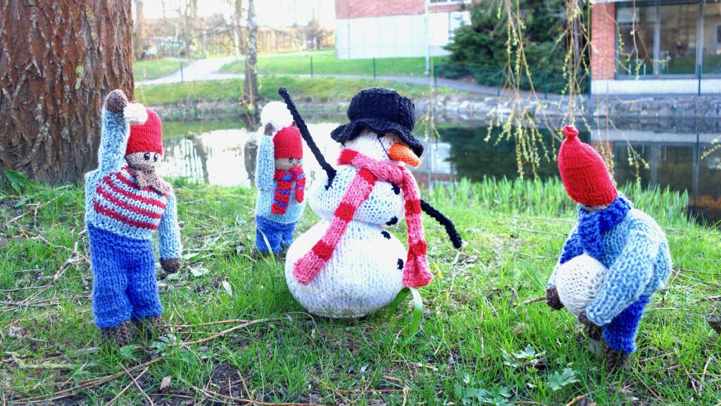 Vid dammen står dessa trevlig figurer som påminner oss om de kalla vintermånader som just har lämnat oss.Figurerna föreställer en snögubbe och tre barn i form av stickade kläder som fyllts för att ge rätt form. Foto: Leif Persson
